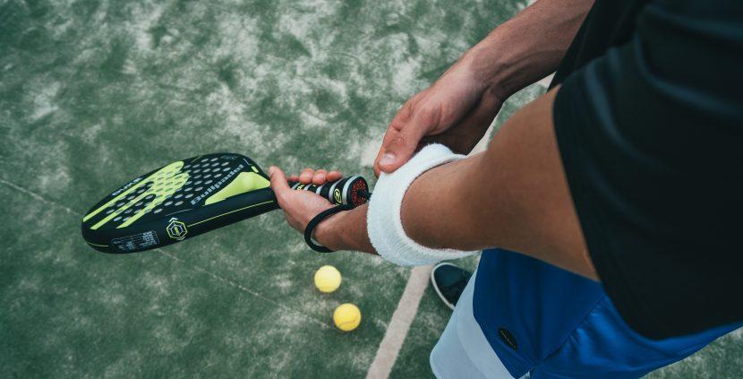 Łokieć tenisisty trzymającego rakietę w ręku