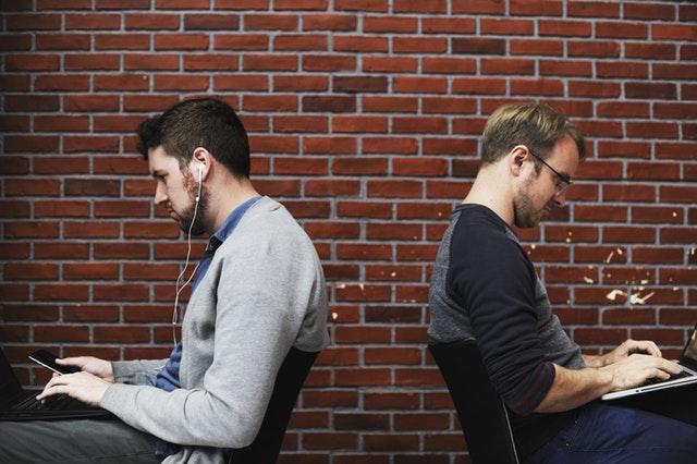 Mężczyźni przy komputerach w pozycji siedzącej - praca biurowa
