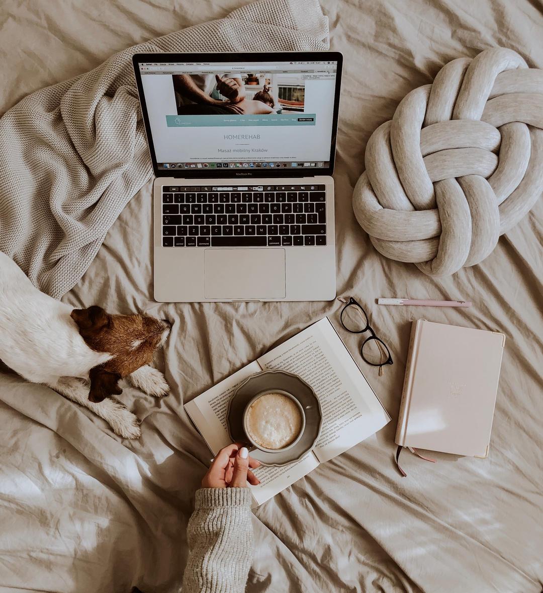 Strona HomeRehab na ekranie laptopa. W otoczeniu znajdują się pies, kawa, książka, okulary.