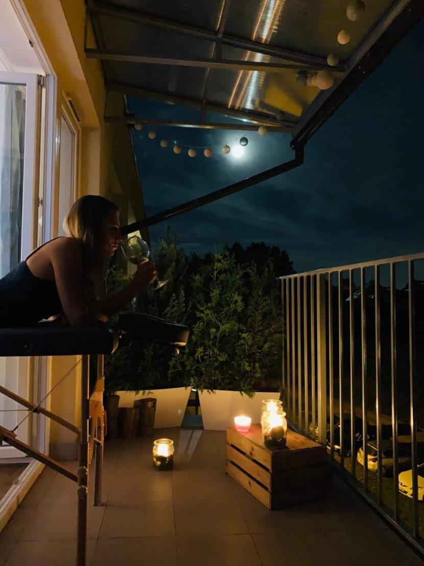 Dziewczyna na stole do masażu, na balkonie, w tle ciemne niebo